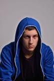 Porträt des überzeugten jungen Mannes, der blaues mit Kapuze Sweatshirt trägt Stockfotografie