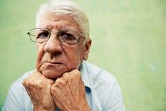 Porträt des ernsten alten Mannes, der Kamera mit den Händen auf Kinn betrachtet Stockfotos