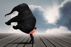 Porträt des Geschäftsmannes schweren Elefanten tragend Lizenzfreies Stockfoto