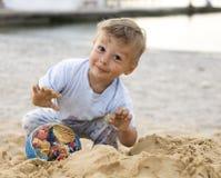 Porträt des glücklichen kleinen Jungen, der auf Strand mit Sand genießt Lizenzfreie Stockfotografie