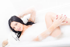 Porträt des glücklichen lächelnden Lügens der schönen sexy verlockenden jungen des Brunette Frau der blauen Augen im Whirlpool, d Stockbild