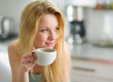 Porträt des glücklichen trinkenden Kaffees der jungen Frau Stockfotos