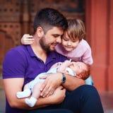Porträt des glücklichen Vaters mit neugeborenem Baby und Sohn Stockfotografie