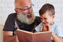 Porträt des Großvaters und sein kleiner Enkel, der ein Buch zu liest Stockfotos