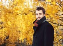 Porträt des hübschen bärtigen Mannes, der einen schwarzen Mantel im Herbst trägt Stockfotos