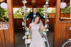 Porträt des hübschen Bräutigams stehend hinter der schönen Braut, die auf Schwingen sitzt Lizenzfreies Stockbild