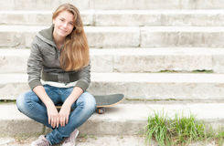 Porträt des hübschen Mädchens mit dem Skateboard im Freien. Lizenzfreies Stockbild