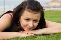 Porträt des jungen Brunettemädchens, das auf einem Gras liegt Lizenzfreie Stockfotos