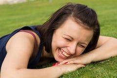 Porträt des jungen Brunettemädchens, das auf einem Gras liegt Lizenzfreie Stockbilder