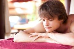 Porträt des jungen gutaussehenden Mannes entspannend im Badekurort Lizenzfreie Stockfotografie