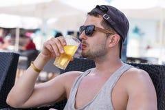 Porträt des jungen gutaussehenden Mannes kaltes Auffrischungsbier trinkend Stockfotografie