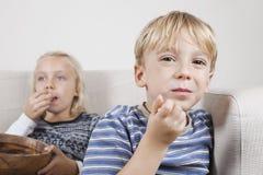 Porträt des Jungen mit der Schwester, die fernsieht und Popcorn isst Stockbild