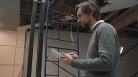 Porträt des kaukasischen Ingenieurs Dokumente auf Tablet-Computer im Einkaufszentrum überprüfend stock video footage