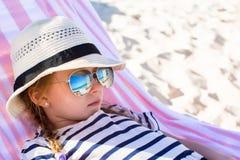 Porträt des kleinen entzückenden Mädchens, das auf Strandruhesessel liegt Stockfotografie