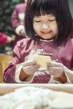 Porträt des kleinen Mädchens Mehlklöße in der traditionellen Kleidung machend Lizenzfreie Stockfotografie
