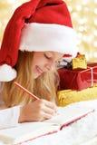 Porträt des kleinen Mädchens mit Weihnachtsgeschenken auf dem goldenen backg Lizenzfreies Stockbild