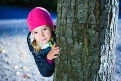 Porträt des kleinen Mädchens versteckend hinter einem Baum Stockfotos