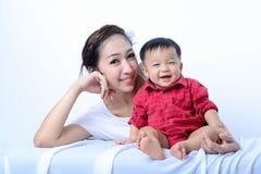 Porträt des Lachens der asiatischen Mutter und des Sitzens des Babys auf Bank Lizenzfreies Stockbild