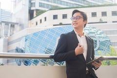 Porträt des lächelnden Geschäftsmannblickes überzeugt unter Verwendung der Computertablette Stockbild