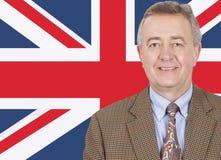 Porträt des lächelnden Geschäftsmannes von mittlerem Alter über britischer Flagge Stockbild