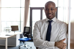 Porträt des lächelnden jungen Geschäftsmannes mit den Armen kreuzte das Lehnen auf Schrank im Büro Lizenzfreie Stockfotografie