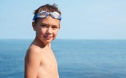 Porträt des lächelnden Jungen mit Gläsern für das Schwimmen Stockfoto
