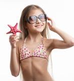 Porträt des lächelnden Mädchens in der Sonnenbrille, die mit Starfish aufwirft Stockfotografie