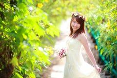 Porträt des lächelnden schönen Brautgriffblumenstraußes in ihren Händen Lizenzfreie Stockbilder