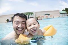 Porträt des lächelnden Vaters und des Sohns im Pool im Urlaub Lizenzfreies Stockfoto