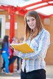 Porträt des Lehrers Standing In Playground mit Ordner Stockfotografie