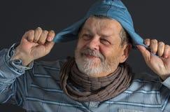 Porträt des älteren Mannes im blauen Hemd und in der Kappe, die wie ein Kind glücklich ist Stockbild