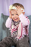 Lustiges Baby mit den Händen auf ihrem Kopf Stockbild