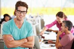 Porträt des Mannes stehend im beschäftigten kreativen Büro Lizenzfreie Stockfotos