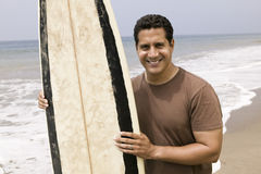 Porträt des Mannes Surfbrett auf Strand halten Lizenzfreies Stockfoto
