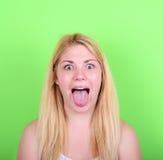 Porträt des Mädchens mit lustigem Gesicht gegen grünen Hintergrund Stockfoto
