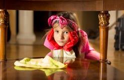 Porträt des müden traurigen Mädchenreinigungsholztischs Stockbilder