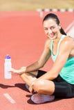 Porträt des müden weiblichen Athleten, der mit Wasserflasche sitzt Lizenzfreie Stockfotos