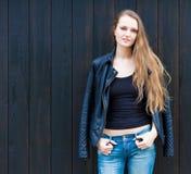 Porträt des modischen sexy Mädchens, das am schwarzen hölzernen Wand-Hintergrund steht Städtisches Mode-Konzept Kopieren Sie Plat Stockbild