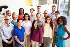 Porträt des multikulturellen Büropersonals stehend in der Lobby Stockbild