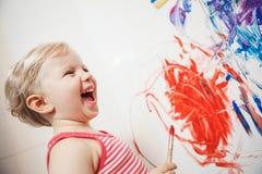 Porträt des netten entzückenden weißen kaukasischen Mädchens des kleinen Jungen, das mit Farben auf Wand im Badezimmer spielt und Stockbild