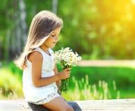 Porträt des netten Kindes des kleinen Mädchens mit Blumenstrauß blüht Stockbild