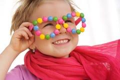 Porträt des netten kleinen Mädchens, das lustige Gläser, verziert mit bunten Alleswissern, Süßigkeiten trägt Stockfoto