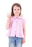 Porträt des netten recht kleinen Mädchens, welches das okayzeichen an lokalisiert zeigt Stockbild