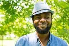 Porträt des netten schwarzen Mannes des Afroamerikaners, der auf Natur lächelt Stockfotografie