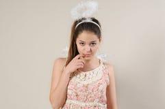 Porträt des netten sehr schüchternen Engelsmädchens mit dem Finger nahe ihrem Mund Lizenzfreie Stockfotografie