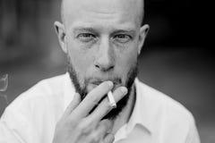 Porträt des Rauchens des jungen roten Haarmannes mit dem Bart Schwarzweiss Stockfoto