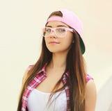 Porträt des recht jungen kühlen Mädchens, das ein Rosa trägt, kleidet Stockbild