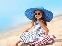 Porträt des recht kleinen Mädchens in einem gestreiften Kleid und in einem Strohhut Stockbild