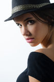 Porträt des schönen Brunettemädchens im schwarzen Hut und in der schwarzen Strickjacke Stockfotos
