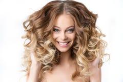 Porträt des schönen jungen lächelnden Mädchens mit dem luxuriösen Haarwinden Stockfotos